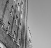Downtown Building Black and White. The side of a building in a busy downtown up against the sky in black and white Stock Photos