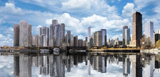 Downtown Chicago Cityscape Skyline Reflections. Downtown Chicago skyline during the fall, casting reflections of its cityscape buildings and cloud filled sky stock photos
