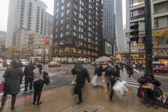 Downtown Chicago. CHICAGO, USA - OCTOBER 30, 2013: All types of people hustle about during the evening rush hour on a drizzly fall day at the intersection of Stock Images