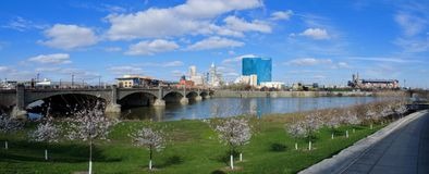 Downtown City Skyline Indianapolis Indiana White River in spring with blooming trees and vegetation, pedestrian bridges and ruins. royalty free stock images