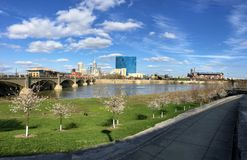 Downtown City Skyline Indianapolis Indiana White River in spring with blooming trees and vegetation, pedestrian bridges and ruins. USA royalty free stock photos