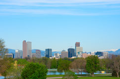 Downtown Denver panoramic skyline buildings with snowcapped mountains and trees Stock Images