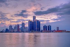 Downtown Detroit, Michigan At Sunset. The setting sun lights up the clouds behind the skyline of downtown Detroit, Michigan. The spectacle is reflected in the stock images
