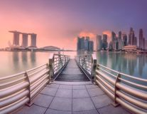 Downtown district and Marina bay in Singapore. View of downtown district and skyline of Singapore from pier with chrome handrails during purple sunset Stock Photos