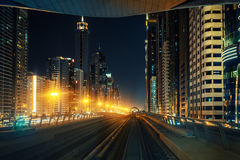 Downtown Dubai skyline by night seen from metro train Stock Photos