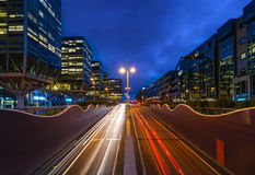 Downtown Leiden. Rush hour in a busy city in the early morning. Cars passing by leaving light trails inbetween the modern Architecture Stock Photo