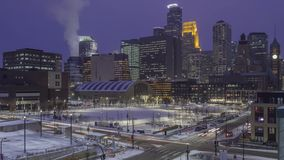 Downtown Minneapolis behind Commons Park and City Street Traffic during a Winter Rush Hour during Twilight. A 4k timelapse shot of traffic passing under the stock video