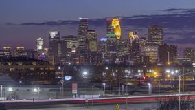 Downtown Minneapolis illuminates during twilight compressed against long exposure traffic and dramatic twilight Light 4K UHD Timel. A timelapse telephoto shot of stock video footage