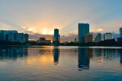 Downtown Orlando buildings in front of Eola Lake Park on beatiful sunset.