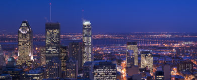 Downtown panorama skyline montreal at dusk. Cityscape with skyscrapers lights on and saint lawrence river and bridge and suburban area in background, the lights Royalty Free Stock Photos