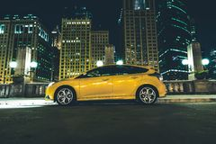 Downtown Parked Car. At Night. Downtown Chicago Parking Space. Five Doors Yellow Car with Lights On Stock Images