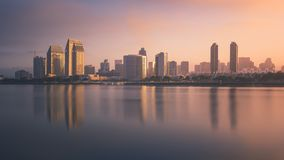 Downtown San Diego reflection on the water during sunrise. Long exposure of the San Diego skyline at sunrise as the buildings are reflected on San Diego bay stock images