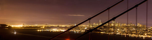 Downtown San Francisco, through Golden Gate Bridge. San Francisco's night skyline, as well as the Bay Bridge and a ferry, are seen through the cables of the Royalty Free Stock Images