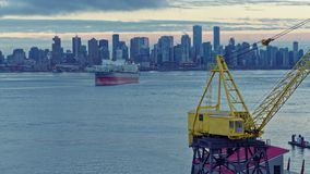 Downtown Vancouver bay, busy morning view, time lapse 4k. Cargo ship and port crane lights. Ship moored in vancouver bay in the morning, view of downtown and stock footage