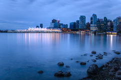 Downtown Vancouver at Twilight with the Bay in Foreground. View of Vancouver Downtown form Stanley Park at Twilight. Some Seashore Rocks are in Foreground Stock Image