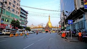 Downtown of Yangon, Myanmar. YANGON, MYANMAR - FEBRUARY 14, 2018: The view on golden Sule Pagoda from the busy Maha Bandula road, one of the central streets of stock video