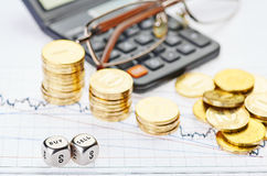 Downtrend штабелирует монетки, чалькулятор, стекла и dices кубики Стоковое Изображение RF