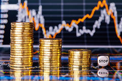 Downtrend financial chart, stacks of golden coins and dices cube Stock Image