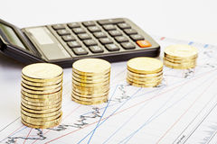 Downtrend stacks of coins, a calculator on the financial chart. Stock Image