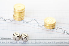 Downtrend stacks of coins and dices cubes Stock Photos