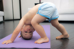 Downward facing dog pose by baby boy Stock Images