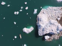 Downward looking drone image of a small research boat collecting ocean measurements near a large and sediment laden iceberg. Drone aerial image during iceberg stock photos