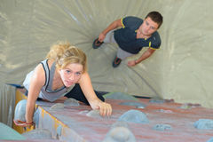 Downward view lady on climbing wall. Downward view of lady on climbing wall stock image
