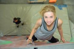 Downward view woman on climbing wall. Downward view of women on climbing wall stock images