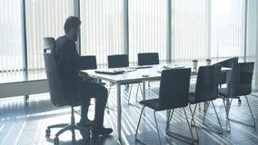Dowodzi 30s w formalnym kostiumu siedzi samotnie w zaświecającym biurze, pracuje na laptopie zbiory wideo