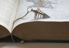 Dowsing with an old medical book Stock Photo