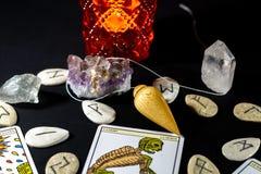 Dowsing Pendulum with Amethyst & Quartz. A dowsing pendulum with various crystals, tarot cards & runes Stock Photo