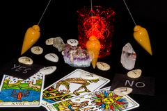 Dowsing Pendulum in 3 Positions. Dowsing Pendulum with Runes, Tarot and YES, NO cards Royalty Free Stock Photos