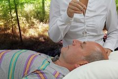 Dowsing the Third Eye under the trees. Female Crystal Therapist dowsing male patient's third eye under the shade of the trees Stock Photo