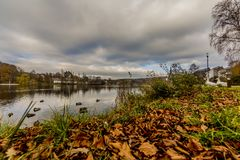 The Doyards Lake with ducks swimming and geese on the grass in Vielsalm royalty free stock image