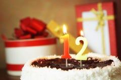 Doze anos de aniversário Bolo com vela e os presentes ardentes Fotografia de Stock