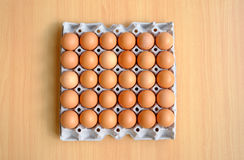 A dozen brown eggs in a carton on a wooden table. Dozen brown eggs in a carton on a wooden table Royalty Free Stock Image