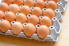 A dozen brown eggs in a carton on a wooden table. Dozen brown eggs in a carton on a wooden table Stock Photography