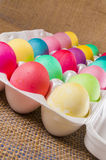 Dozen colored Easter eggs,carton,burlap Stock Photography