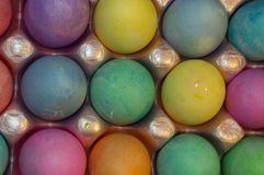 A perfectly, colored dozen of eggs placed in an egg carton for the easter holiday Royalty Free Stock Photography
