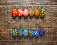 Dozen colorful painted Easter eggs on wooden background Stock Photos
