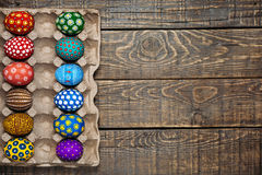 Dozen colorful painted Easter eggs on wooden background Royalty Free Stock Image