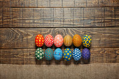 Dozen colorful painted Easter eggs on wooden background Royalty Free Stock Images