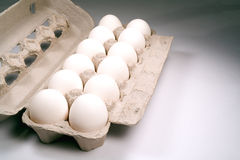 A dozen eggs. A dozen clean white eggs in a carton against a gray backdrop Royalty Free Stock Image