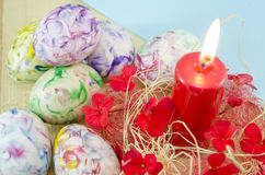 Dozen of handcolored Easter eggs and a burning candle Stock Photos