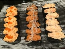A dozen of 3 kinds Gunkan salmon sushi. On the Japanese plate Royalty Free Stock Photos
