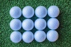 Dozen Golf Balls. Dozen new golf balls on turf Royalty Free Stock Photography