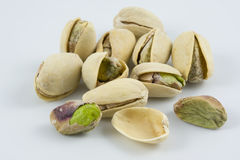 Dozen of salted and roasted pistachio nuts. On white background, focus on front row Royalty Free Stock Images