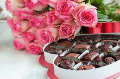 Beautiful Soft Pink Roses with a Heart Shape Box of Chocolate Candy. Dozen soft pink rose flowers with a heart shaped box of chocolate candy for Valentine Day stock photos