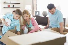 Dozen van het familie de uitpakkende karton in nieuw huis royalty-vrije stock afbeeldingen