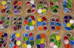 Dozens of well used paint cups and paintbrushes with vividly col Stock Images